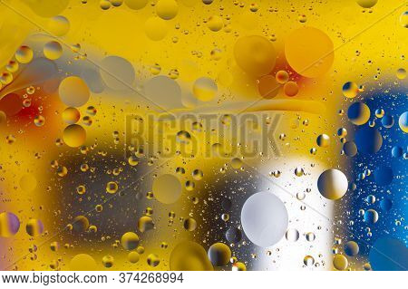 The Hue Abstract Composition With Oil Drops In Water. Yellow, Blue, White Colors.