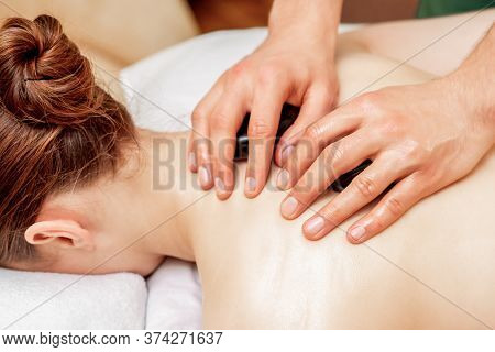Hands Of Massage Therapist Doing Back Massage With Massage Stones On Back Of Woman Close Up.