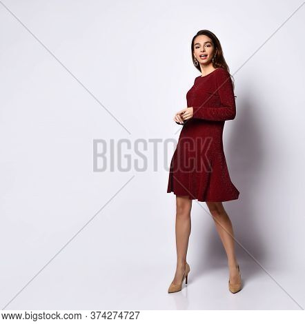 Gorgeous Dark-haired Young Woman Standing In Heels, In An Elegant Dress With Sequins, With Long Slee