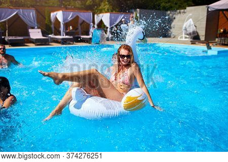 Young Smiling Bikini Girl Having Fun With Friends On Inflatable Swan In Swimming Pool. Happy People