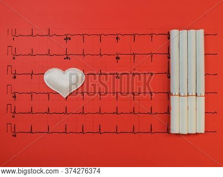 A White Heart And Cigarettes Lies On A Printout Of The Results Of A Cardiogram On A Red Background.