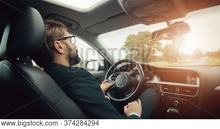 Rear View Of Businessman Resting Or Sleeping On Drivers Seat Staying In Car On Country Roadside