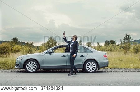 Businessman Walking Around Car On Roadside In Country Area Holding Phone Looking For Mobile Network