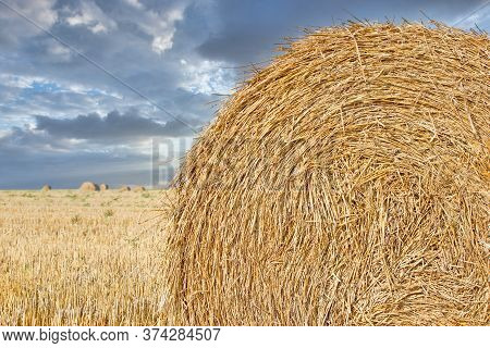 Straw Bale On Agricultural Field And Dramatic Cloudy Sky, Beautiful Landscape After Harvest, Straw R