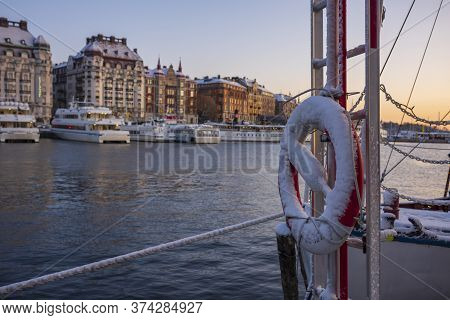A Snow Covered Life Preserver, Stored On A Water Taxi That Is Docked In A Harbor In Stockholm, Swede