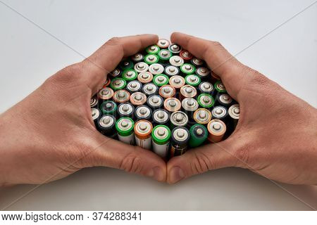 Close Up Of Hands Holding Many Alkaline Batteries On White Background. Concept Of Recycling Waste An