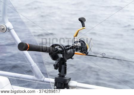 Fishing Rod Spinning With The Line Close-up. Fishing Rod In Rod Holder In Fishing Boat. Fishing Rod