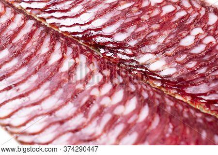 Top View Of Smoked Pork Salami Chorizo Sausages Slices Background. Raw Smoked Salami Sausage
