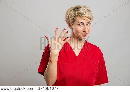 Portrait Of Young Attractive Female Nurse Showing Number Five