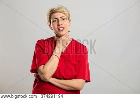 Portrait Of Young Attractive Female Nurse Holding Hurting Throat