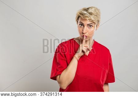 Portrait Of Young Attractive Female Nurse Making Silence Gesture