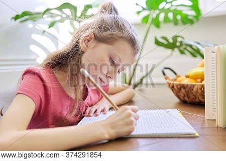 Kid Girl Studying At Home, Sitting At The Desk, Writing In School Notebook. Homework, Distance Learn