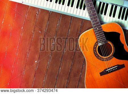 Musical Instrument - Closeup Midi Piano 61 Key Keyboard And Vintage Acoustic Guitar On A Wooden Back