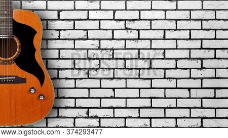 Musical Instrument - Silhouette Of A Vintage Acoustic Guitar On A White Brick Wall Background.