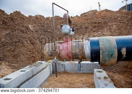Laying Heating Pipes In A Trench At Construction Site. Installation Underground Storm Sewer Pipes Of