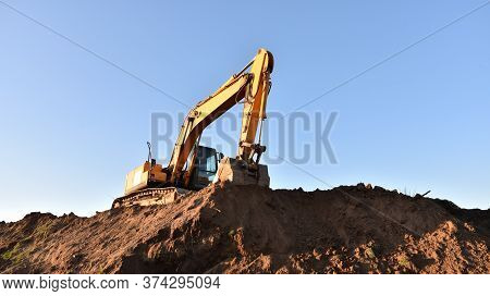 Excavator Working At Construction Site. Backhoe Digs Ground In Sand Quarry On Blue Sky Background. C