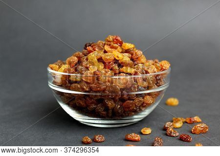 Raisins In A Glass Transparent Bowl On A Black Background