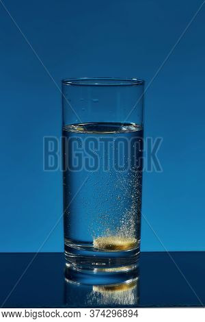 Close Up Of Glass Of Water With Effervescent Aspirin Tablet, Pill In It Isolated Over Blue Backgroun