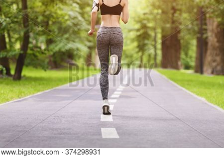 Unrecognizable Female Jogger Running On Path In Green City Park, Rear View, Cropped Image With Free