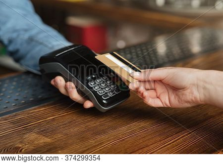 Quick And Easy Pay Bill. Female Customer Pays For Drinks With Credit Card At Terminal On Wood Bar, C