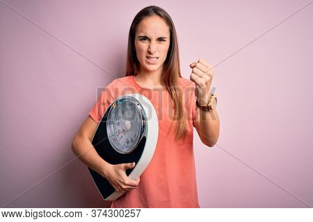 Young beautiful woman controlling weight holding weighting machine over pink background annoyed and frustrated shouting with anger, crazy and yelling with raised hand, anger concept