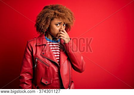 Young beautiful African American afro woman with curly hair wearing casual red jacket smelling something stinky and disgusting, intolerable smell, holding breath with fingers on nose. Bad smell