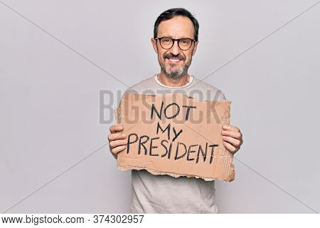 Middle age handsome man on disagreement holding banner with not my president message looking positive and happy standing and smiling with a confident smile showing teeth