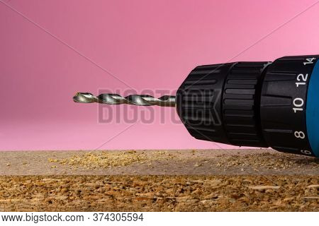 Electric Drill With A Drill On A Pink Background