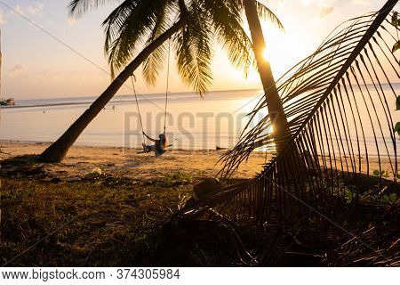 The Girl On The Beach Rides On A Swing During Sunset. Sunset In The Tropics, Enjoying Nature. Swing