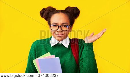I Hate School. Unhappy Black Girl Spreading Hands Over Yellow Background, Panorama, Free Space