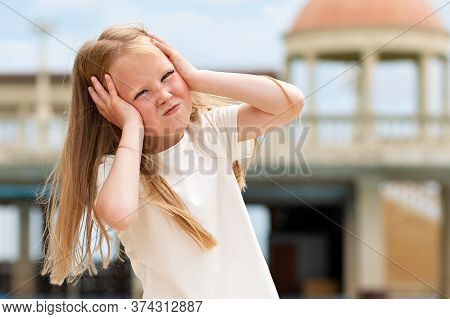 Emotions. Portrait Of A Little Girl Showing Her Frustration And Discontent. In The Background Is A B