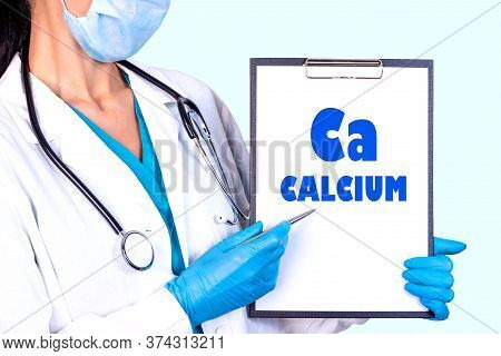 Calcium Ca Text Is Written On A Tablet Which The Doctor Holds In A Medical Gown And Gloves. Medical