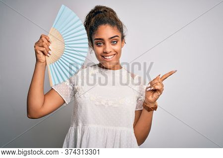 Young african american girl using hand fan to refreshment over isolated white background very happy pointing with hand and finger to the side