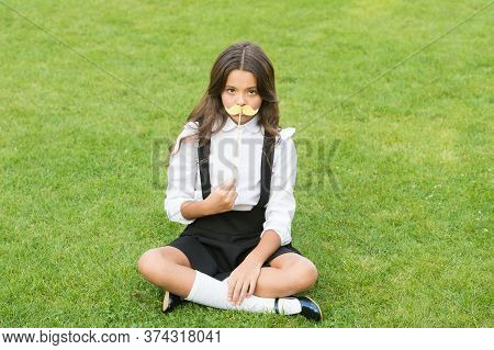 Cute Mustache. Small Girl Hold Fake Mustache On Face. Happy Childhood. Little Child School Uniform.
