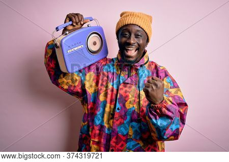 Young african american man listening to music holding portable vintage retro radio screaming proud and celebrating victory and success very excited, cheering emotion