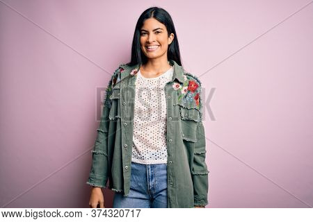 Young beautiful hispanic fashion woman wearing cool jacket over pink background with a happy and cool smile on face. Lucky person.