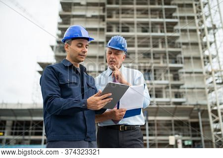 Architect and site manager using a tablet in front of a construction site