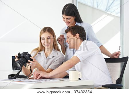 Female photographer viewing images on camera with her team in the office