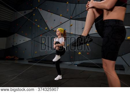 Active Little Girl Going To Climb, Female Instructor Helping Her To Warm Up Against Artificial Train