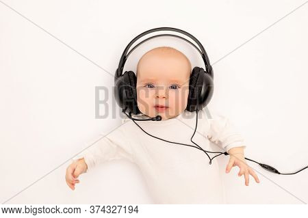 Portrait Of A Child On A White Background With Headphones. Stay Home, Coronavirus 19. Baby 6 Months