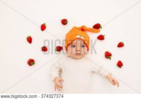 Cute Girl In A White Bodysuit On A White Isolated Background Eating A Strawberry, First Feeding, Bab
