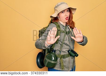 Young redhead backpacker woman hiking wearing backpack and hat over yellow background Moving away hands palms showing refusal and denial with afraid and disgusting expression. Stop and forbidden.