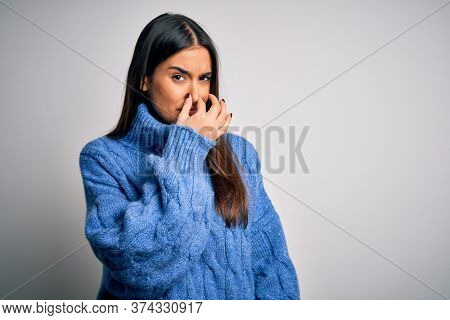 Young beautiful brunette woman wearing casual turtleneck sweater over white background smelling something stinky and disgusting, intolerable smell, holding breath with fingers on nose. Bad smell