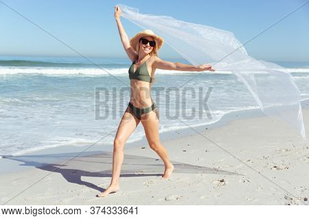 Attractive blonde Caucasian woman enjoying time at the beach on a sunny day, holding and waving transparent material, with blue sky and sea in the background. Summer tropical beach vacation.