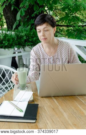 Woman Freelancer Or Blogger Sitting At The Work Place With Cup Of Green Matcha Late Coffee Or Tea. C
