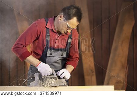 Middle-aged Male Craftsman In Protective Googles Working On Workpiece With Electric Planer On Workbe