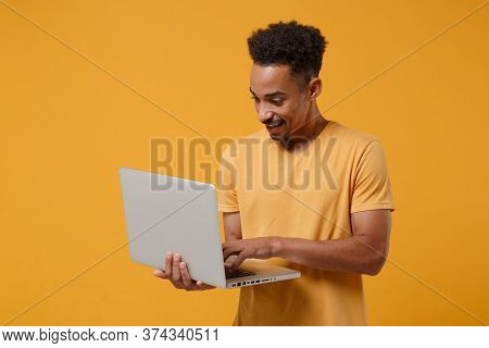 Smiling Young African American Guy In Casual T-shirt Posing Isolated On Yellow Orange Wall Backgroun