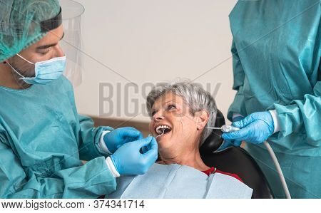 Man Dentist Operating Senior Woman In Dental Clinic - Oral Healthcare Assistance Concept