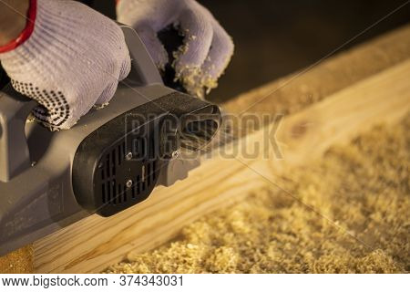 Closeup Crop Hands Of Woodworker Making Wooden Detail And Using Electric Plane At Workplace Covered