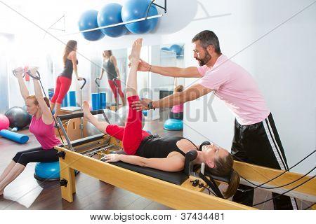 Homem de instrutor de aeróbica personal trainer Pilates em cadillac fitness mulher exercício